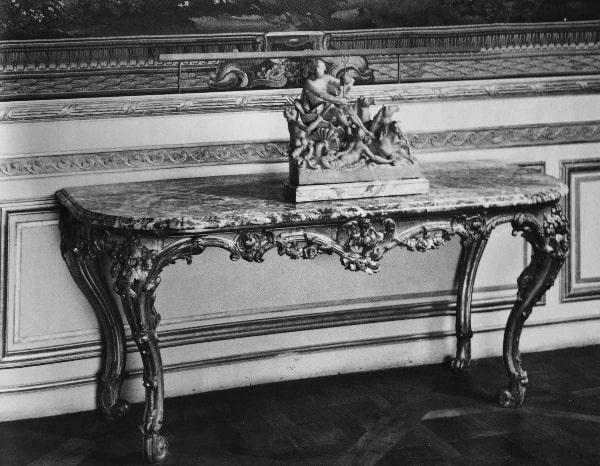 זוג שולחנות קיר (קוסולות), צרפת 1750 בקירוב.השולחנות עשויים עץ מגולף ומוזהב עם לוח שיש המותקן מעליהם, אחד השולחנות מקורי ונעשה ב-1759 בקירוב, השולחן השני הוא העתק שלו. הרגליים מעוקלות ומגולפות בדגמי מגילות ופרחים, לוח השולחן חדש ועשוי מיציקת שיש סגול.