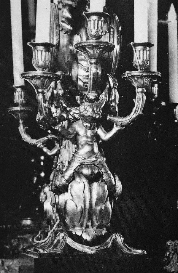 זוג פמוטים,צרפת, 1785 בקירוב.משויך לקלודיוןברונזה מוזהבת, שישלכל פמוט ארבע זרועות והוא נישא בידי ילד מברונזה מושחמת הניצב על כן עגול משיש כחלחל אפור מעוטר באפריז של דגם שריגים וקופידונים.