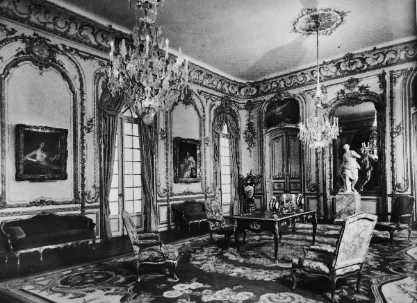 מבט על הסלון שבו רואים את הקיר עם דלתות הגן, אחת משלושת המראות המותקנות בחדר והלוחות המעוטרים במונגרמות של סמואל ברנאר הרוזן דה קובר.