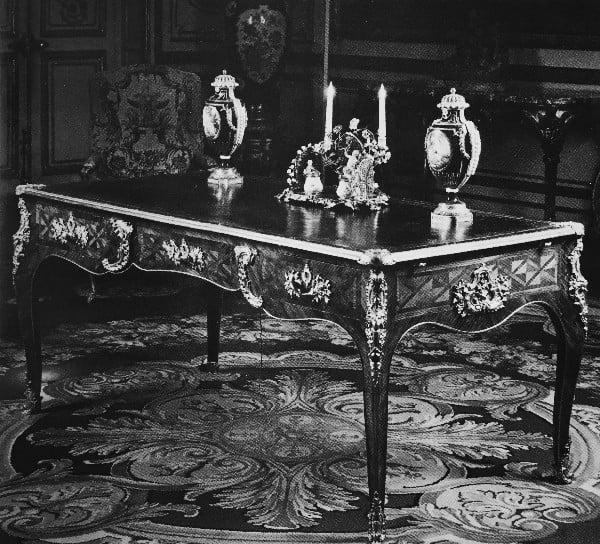 שולחן כתיבה, משויך לאבניסט פייר מיז׳ון השני, צרפת 1740 בקירובהשולחן עשוי מעץ המעוטר בשיבוץ בדגם גיאומטרי מעץ ורדים ועץ אדום, מעוטר בהתקני ברונזה מוזהבת: כרטושים, תליונים, פרזול לרגליים, ידיות למגירות ומנעולים. לוח השולחן מצופה עור מעוטר בהטבעה, בחזית השולחן שלוש מגירות ובגבו לוח זחיח ושתי מגירות סתר.
