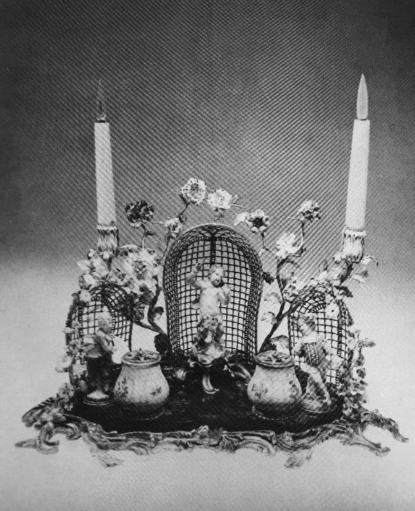 כן לקסתות דיו ועליו זוג פמוטים, תקופת לואי ה-15.מגש מצופה לכה יפנית מעוטרת בצבע בתוך מסגרת ברונזה מגולפת ומוזהבת. על המגש שתי קסתות לדיו וכן שלוש דמויות ופרחים, כולם מחרסינה. משני צידי הכן זוג פמוטים.