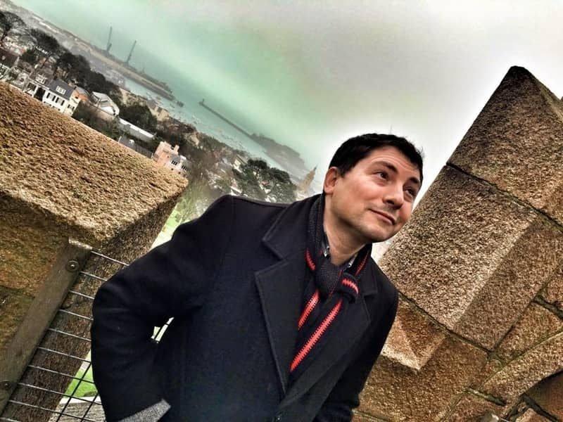 אני על ראש מגדל ויקטוריה בגרנזי. מאחורי ניתן לראות את העיירה, הנמל והים.