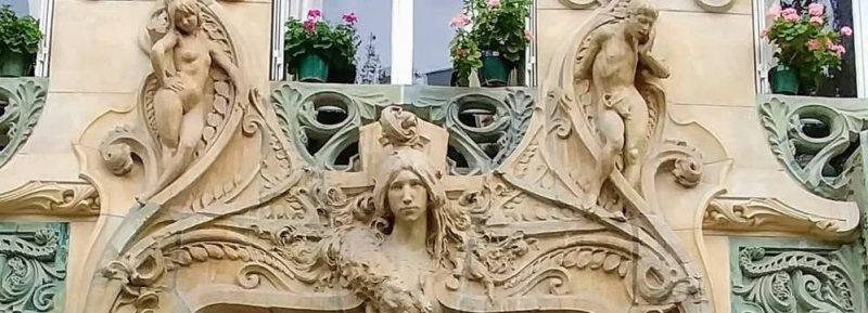 החל העליון של הכניסה לבניין ברחוב Rapp. אדם וחווה נמצאים משני הצדדים ובאמצע ראשה של אשתו של אדריכל הבניין. צילום: יואל תמנליס.
