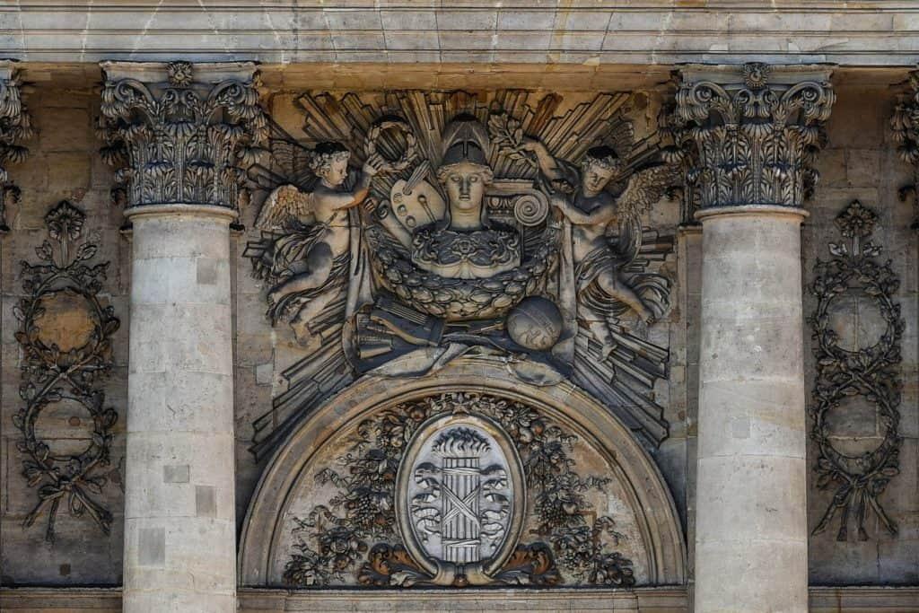 מזכרת בחזית בניין הקולז' דה פראנס מהימים ששכנו בו חדרי סטודיו של ציירים. למטה אנו רואים את אגד הזרדים, סמל מהפכני רפובליקני ולמעלה אנו רואים את כלי העבודה של הציירים.  צילם: יואל תמנליס